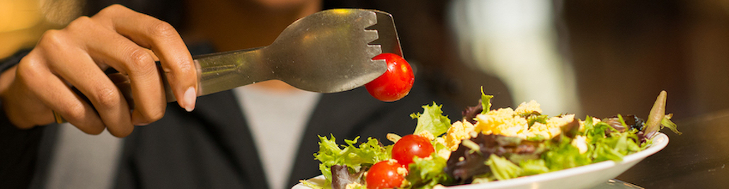 A hand placing a grape tomato onto their plate of salad.